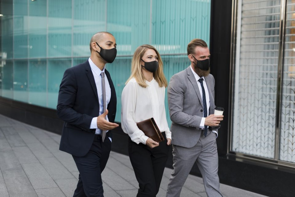 Business people in medical masks walking to the office